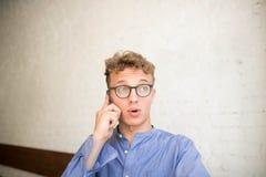 Homem confuso do moderno que fala através do telefone celular, sentando-se no interior moderno contra a parede de tijolo fotografia de stock