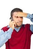 Homem confuso que fala pelo móbil do telefone Fotografia de Stock Royalty Free