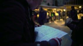 Homem confuso que olha o mapa de papel, verificando a rota, sentido para tropeçar o destino video estoque