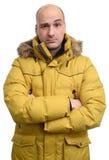 Homem confuso que veste o revestimento amarelo do inverno Fotografia de Stock