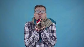Homem congelado coberto na geada e em luvas vestindo e um lenço em um fundo azul video estoque