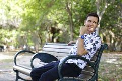 Homem conservado em estoque da imagem que senta-se e que sorri sobre o ombro Fotografia de Stock Royalty Free