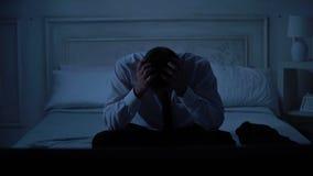 Homem considerável ansioso no terno de negócio que senta-se na cama, mãos de fricção, problemas filme