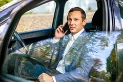 Homem considerável bem sucedido no terno que senta-se no smartphone e no sorriso da terra arrendada do carro fotografia de stock