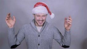 Homem considerável bonito no chapéu de Papai Noel que aprecia a neve, movimento lento filme