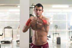 Homem considerável com as luvas de encaixotamento vermelhas no Gym Foto de Stock Royalty Free