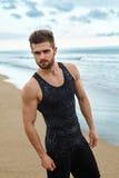 Homem considerável com corpo muscular do ajuste no Sportswear na praia fotos de stock royalty free