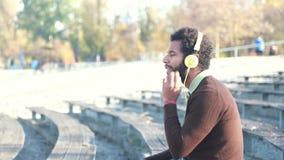 Homem considerável com fones de ouvido que escuta a música video estoque