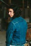 Homem considerável com a morena longa do cabelo em um revestimento da sarja de Nimes Fotografia de Stock Royalty Free