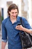 Homem considerável com o cabelo longo que guarda o telefone e o saco espertos imagens de stock