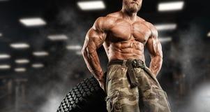 Homem considerável com os músculos grandes, levantando na câmera no gym fotos de stock royalty free