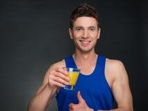 Homem considerável com suco de laranja, t-shirt azul Imagem de Stock