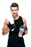 Homem considerável da aptidão que guarda a toalha e a garrafa com água Fotos de Stock Royalty Free