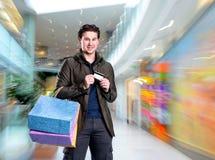 Homem considerável de sorriso com sacos de compras e cartão de crédito Fotografia de Stock Royalty Free