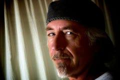 Homem considerável de sorriso que veste um chapéu com o cavanhaque, olhando o visor imagens de stock