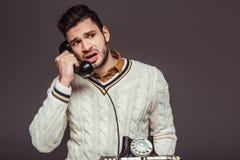 homem considerável denominado retro irritado que fala pelo telefone estacionário do vintage Foto de Stock