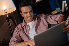 Homem considerável despreocupado que olha através de algumas imagens imagem de stock