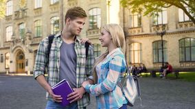 Homem considerável e fêmea novos que estão a faculdade próxima, conversação agradável fotos de stock
