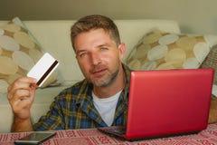 Homem considerável e feliz novo que mantém o cartão de crédito que senta em casa o sofá do sofá usando o sorriso em linha da comp imagens de stock