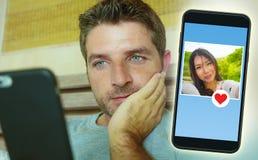Homem considerável e feliz novo que usa meios sociais do Internet no telefone celular que procura o amor que flerta e que data em foto de stock
