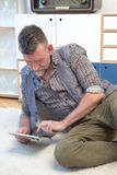 Homem considerável em seu 50s que olha a tabuleta fotografia de stock royalty free