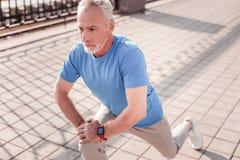 Homem considerável envelhecido que estica os pés que confiam no joelho foto de stock royalty free