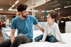 Homem considerável farpado com a filha que senta-se no colchão Escolhendo o colchão na loja fotos de stock royalty free