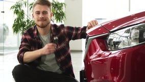 Homem considerável feliz que levanta com seu automóvel novo que mostra chaves do carro à câmera vídeos de arquivo