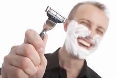 Homem considerável feliz que mostra sua lâmina Fotografia de Stock