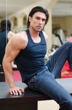 Homem considerável, muscular que senta-se na mesa, com calças de brim e tanktop Imagens de Stock