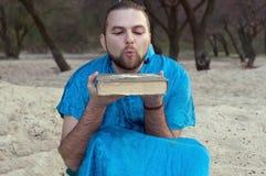 Homem considerável na areia de sopro do quimono azul do livro fotos de stock