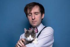 Homem considerável na camisa com os olhos fechados que guardam o gato cinzento bonito imagem de stock