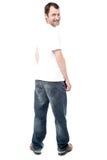 Homem considerável nas calças de brim que estão para trás fotos de stock royalty free