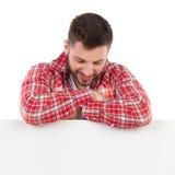 Homem considerável no lenhador vermelho Shirt Is Looking para baixo na bandeira imagens de stock