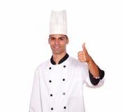 Homem considerável no uniforme do cozinheiro chefe que mostra o bom sinal do trabalho Imagem de Stock