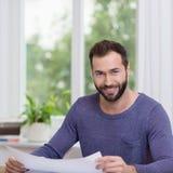 Homem considerável nos azuis marinhos Gray Shirt Holding Paper Foto de Stock