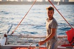 Homem considerável novo, capitão que conduz o iate no mar no dia ensolarado foto de stock royalty free