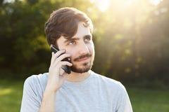 Homem considerável novo com barba grossa e os olhos grandes escuros que guardam o telefone esperto que telefona a seu amigo ao es fotografia de stock royalty free