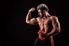 Homem considerável novo com músculos fortes, bebida da proteína após o trai fotos de stock