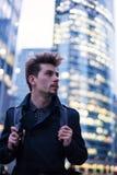Homem considerável novo com a trouxa na cidade moderna grande fotografia de stock royalty free