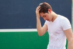 Homem considerável novo do atleta que pausa após o exercício com suor em sua cara no fundo do clube de esporte fotos de stock