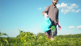 Homem considerável novo do moderno que molha o jardim com uma lata molhando do país vídeos de arquivo