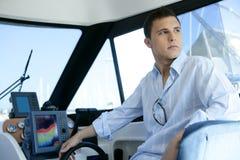Homem considerável novo em um interior do barco do iate Imagens de Stock
