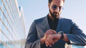 Homem considerável novo em um terno que passa pelo terminal de aeroporto e que usa o relógio esperto Dispositivos modernos, estil filme