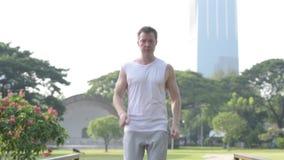 Homem considerável novo feliz que movimenta-se no parque como o conceito vivo saudável vídeos de arquivo
