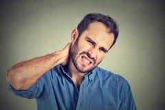 Homem considerável novo forçado, infeliz com dor de pescoço má Fotos de Stock Royalty Free