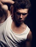 Homem considerável novo forte 'sexy' que levanta no t-shirt branco no drak s fotos de stock royalty free