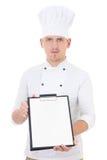 Homem considerável novo na prancheta mostrando uniforme do cozinheiro chefe com placa Imagens de Stock