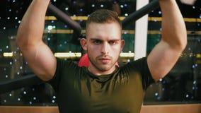 Homem considerável novo no t-shirt militar que dobra os músculos da caixa e que treina seus ombros no gym Exercício no dever vídeos de arquivo