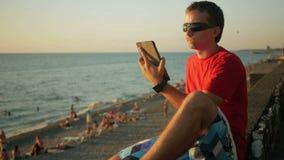 Homem considerável novo nos óculos de sol que relaxam perto da praia do mar com tablet pc Verifica mensagens em redes sociais vídeos de arquivo